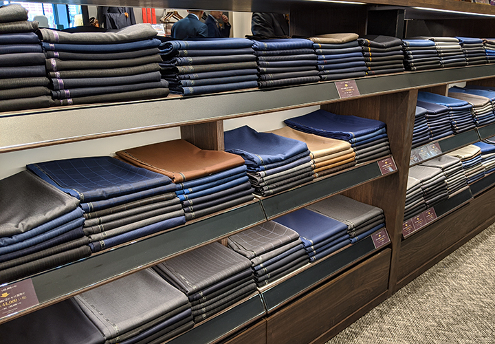 横浜西口店のスーツ什器には色とりどりの生地が並んでいる